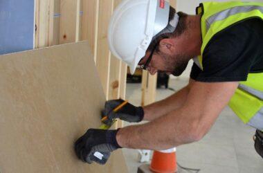 Builder Measuring Plasterboard